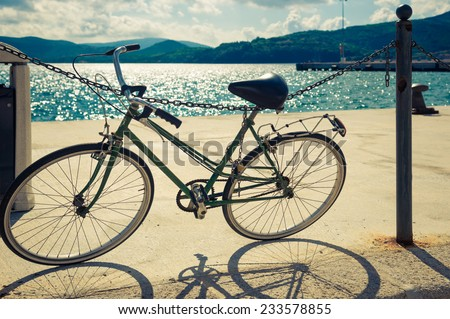 An old bicycle standing near a sea, Italy. Toned image. - stock photo