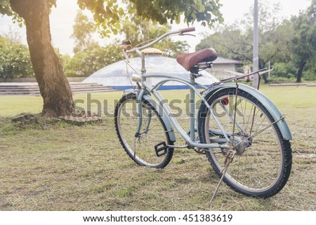 an old bike leaning beside a tree toned with a retro vintage filter app or action effect - stock photo