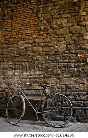 an old bike standing on a brick wall - stock photo