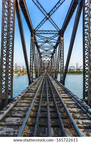An old black metal train bridge over a river