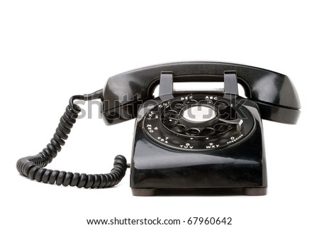 An old black vintage rotary style telephone isolated over a white background. - stock photo