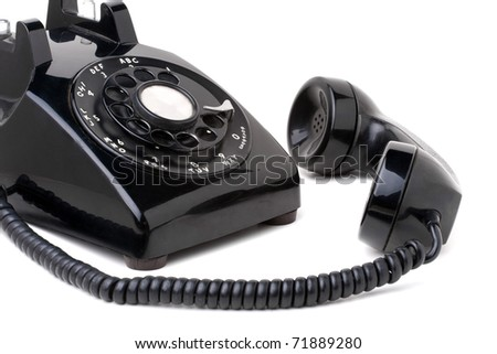 An old black vintage rotary style telephone off the hook isolated over a white background. - stock photo