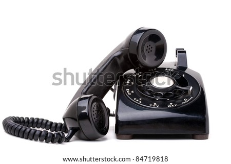 An old black vintage rotary style telephone with the handset off the hook isolated over a white background. - stock photo