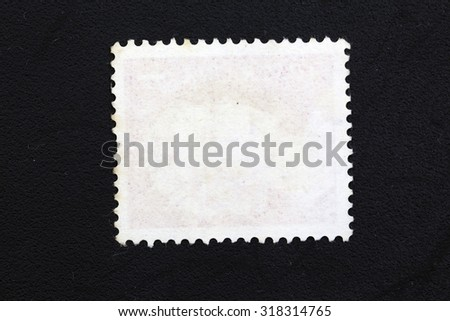 an old Blank postage stamp with one missing perforation on a black background with lager background space - stock photo