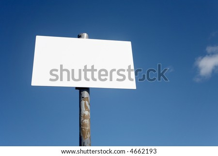 An old blank white sign and a blue sky.