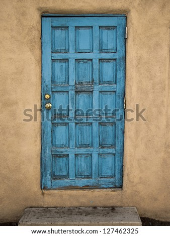 An old blue door in a adobe mud wall portrays an element of decay with layers and layers of peeling paint and cracks. - stock photo