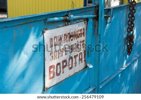 An old, blue iron gate of a closed factory with local dialects written on the signboard, probably prohibiting trespassing. Minsk is rich in industries providing permanent occupation to the residents. - stock photo