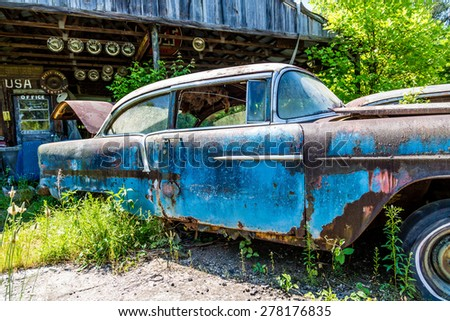 An Old Blue Rusted out car in front of a shed - stock photo