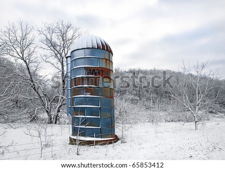 An old blue silo in a very cold, snowy winter scene. - stock photo