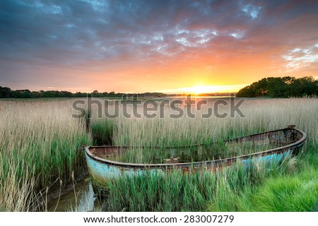 An old boat in reeds at Poole harbour on the Dorset coast - stock photo