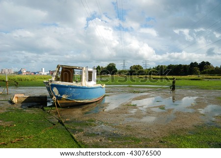 An old boat moored in a tidal inlet of Poole Harbour, Dorset (England) - stock photo