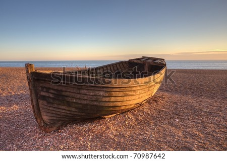 An old boat on Brighton beach by sunset