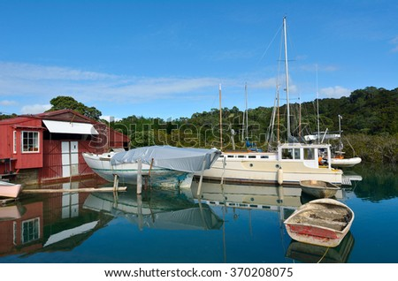 An old boat shed with empty yachts in Leigh, New Zealand. - stock photo