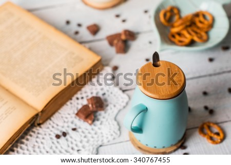 an old book and a cup of coffee with milk and pretzels on vintage wooden table - stock photo