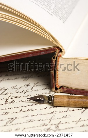 An old book lies open with a pen on top of a hand written document in calligraphy. - stock photo