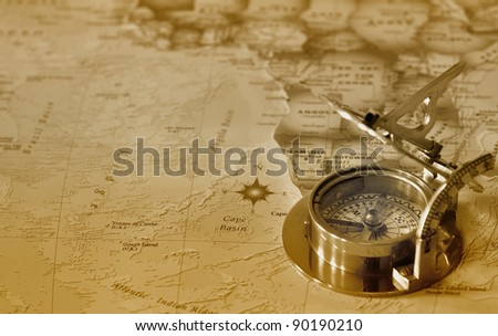 An old brass compass on a map background - stock photo