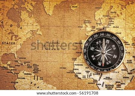 An old brass compass on a Treasure map background - stock photo