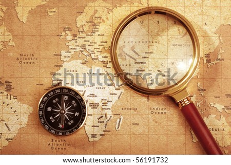 An old brass compass on a Treasure map background ,with Magnifier - stock photo