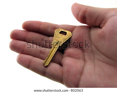 An old brass key in the palm of a man's hand - stock photo