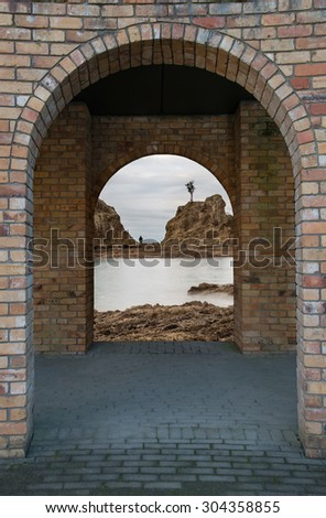 An old brick archway leading through a door into another world. We all daydream and this would be a great photo for anything related to dreaming, magical, mysterious, or other imaginary ideas. - stock photo