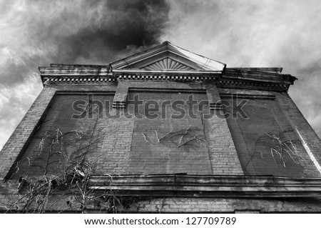 An old brick building stands against a cloudy sky. - stock photo