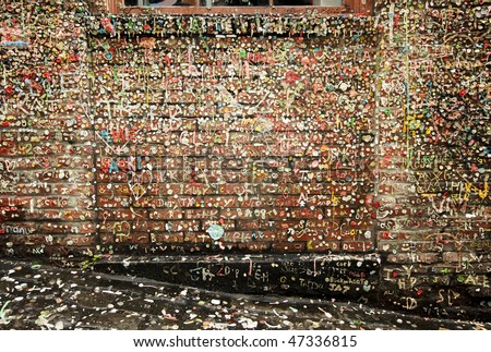 An old brick wall in Post Alley in the Pike Place Market in Seattle is covered with chewing gum deposited over a number of years. The gum is worked into names and other forms of graffiti. - stock photo