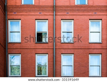An old brick wall with one window open - stock photo
