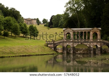 An old bridge with a mansion in the background