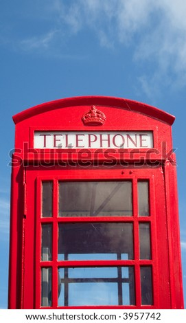 An old British red telephone box and a blue sky. - stock photo