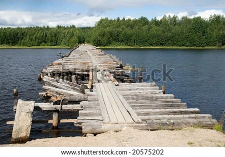 An old broken bridge on a river in Karelia, Russia - stock photo