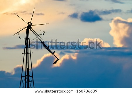 An old broken windmill stands against a cloudy, late evening sky. - stock photo