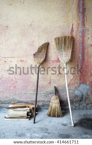 An old broomstick leaning against the wall - stock photo