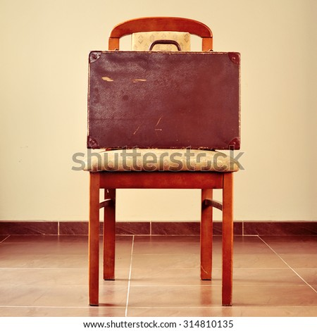 an old brown suitcase on a worn and retro chair - stock photo