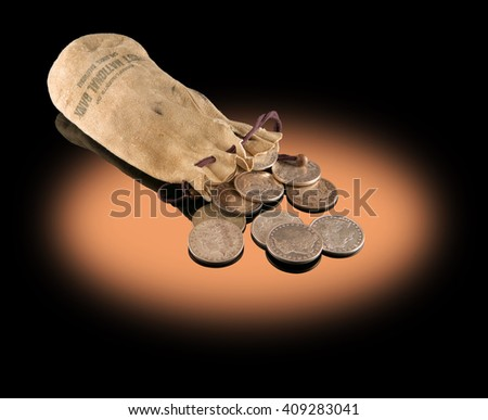 An old buckskin pouch from the nineteenth century holding Morgan silver dollars from that period. - stock photo