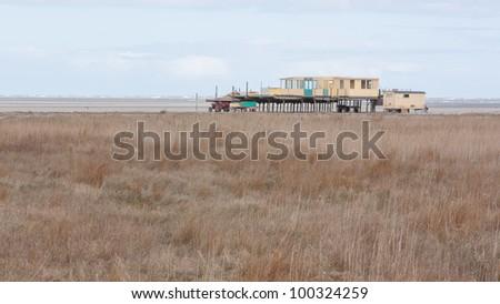 An old building on the dutch beach (Waddensea) - stock photo