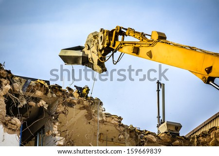An old building will be demolished with excavators. - stock photo