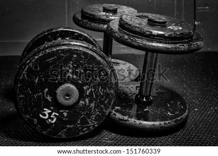 An old but well used set of dumbbells at the gym in black and white. - stock photo