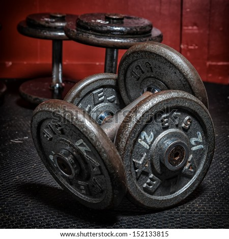 An old but well used sets of dumbbells at the gym. - stock photo