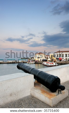 An old cannon pointing at the new harbour on the island of Spetses, Greece