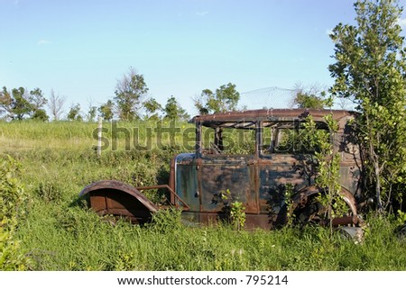 An old car sitting on the prairie forgotten and overgrown with bushes.