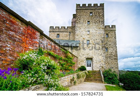 An old castle in England UK with walled garden & flowers - stock photo