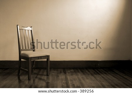 An old chair sits in an empty room - stock photo