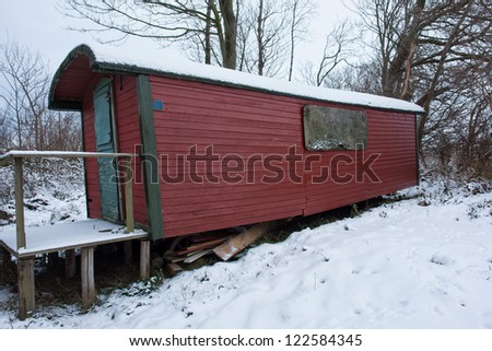 An Old Classical Traditional Gypsy Caravan in a snow covered forest - stock photo