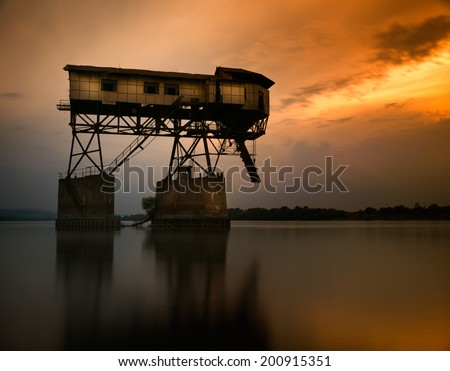 An old coal platform's dream-dilapidated building on the river  - stock photo