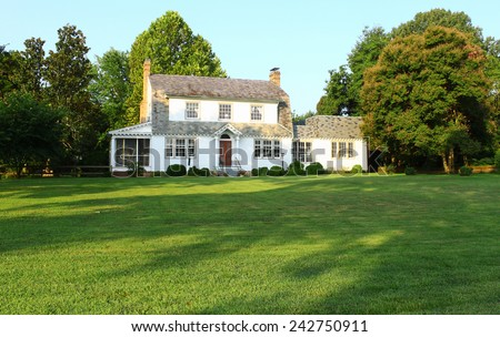 An old Colonial house in Yorktown VA from the late 1800's early 1900's with a large front lawn of lush green grass. - stock photo