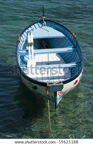 An old colored rowboat anchored in the sea - stock photo