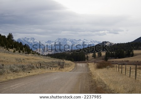 An old country road near Bozeman, Montana. - stock photo