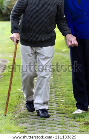 An old couple walk in a street.Concept photo of old age, health care,lifestyle, pensioner, medical, retirement.  - stock photo