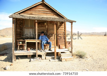 an old cowboy sits on the porch of his home after a hard day of gamblin' n drinkin' n chasin' saloon girls round the piano - stock photo