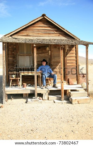 an old cowboy sits on the porch of his home after a hard day of ropin and riding the range - stock photo